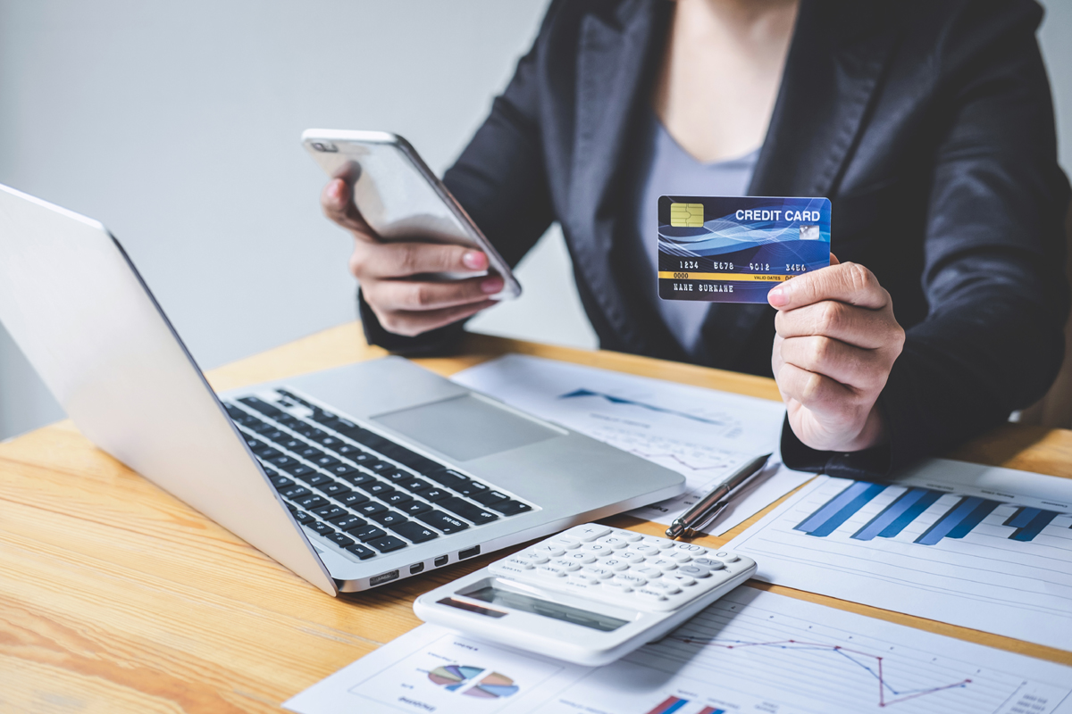 Business woman consumer holding smartphone, credit card and typi